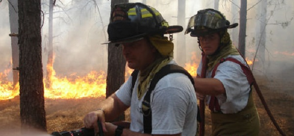 Two firefighters putting out a fire in the woods.